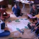 A group of STEP learners are sat on the floor in discussion surrounding a large piece of paper with a drawing representing a tree and cut outs of leaf shapes