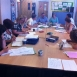 A group of STEP learners sit around a desk in group, some in discussion, some writing into work books