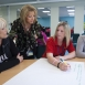 A trainer talks to 3 learners sat at a desk as they write ideas onto a piece of flip chart paper