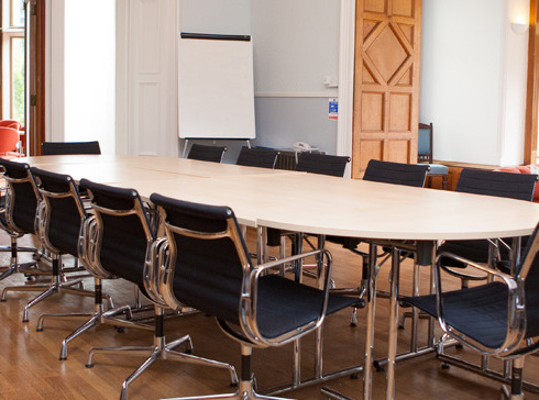 A Nation Star College room with tables and chairs is laid out in a boardroom style