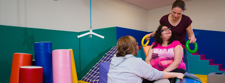 Two therapists work with a student during a occupational therapy session
