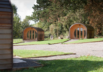 Two rounded camping pods with their own paths in a grass area.