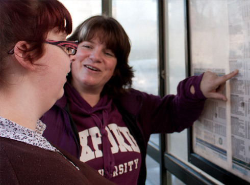 Travel trainer working with a learner at a bus time table