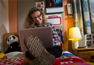 A National Star College student sits on her bed looking at a laptop.