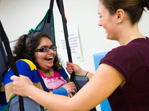 A female student in a hoist with an Occupational Therapist.