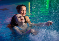 National Star College student in the hydrotherapy pool supported by Physiotherapist.