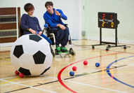 Two residents playing ball games in the sports hall