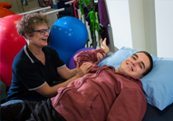 A physiotherapist treats a National Star College student who is lead on a bed.