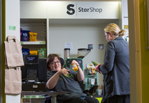 A National Star Student hands customer her items in the Star shop.