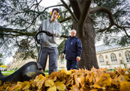 A National Star College student uses a leaf blower on a work placement, supervised by a member of staff
