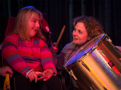 A National Star College music therapist banging a drum with a student.