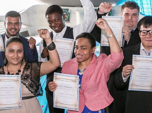 A group of National Star College students hold certificates and punch the air.